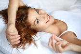 Joyful woman in bed — Stock Photo