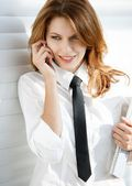 Business woman holding folder in her hand and talking on the phone — Stock Photo