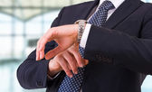 Businessman checking time on his wristwatch. — Stock Photo