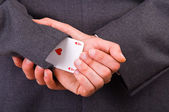Businessman holding playing card behind his back. — Stock Photo