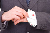 Businessman with playing cards hidden under sleeve. — Stock Photo