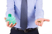 Businessman holding crushed bottle and coins. — Stock Photo