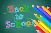Back to school with colors pencils over chalkboard — Stock Photo