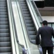 Confident businessmwalking to escalator — Stock Video #27412725