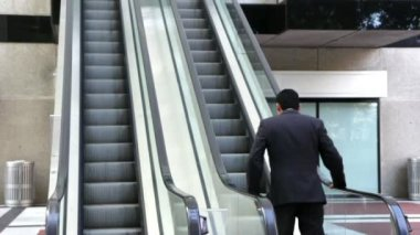 Confident businessman walking to an escalator — Stock Video