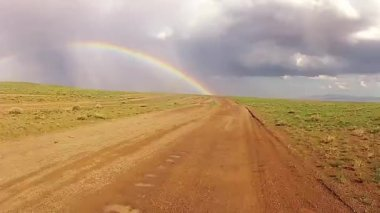 Desert driving on a muddy road with a rainbow in the back — Stock Video