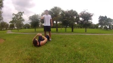 Young man doing sit-ups, exercising with personal trainer — Stock Video