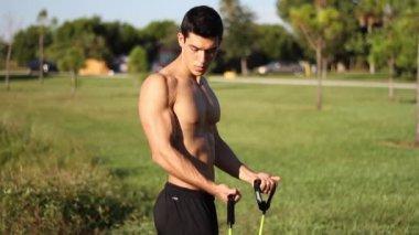 Homem jovem musculoso fazendo exercícios de braço com uma banda de resistência — Vídeo Stock