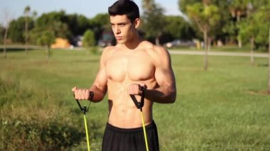 Muscular young man doing arm exercises with a resistance band — Stock Video
