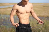 Muscular young man showing abs, — Stock Photo