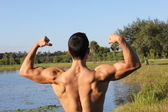 Fit male model showing his biceps and back — Stockfoto