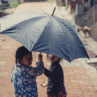 Two Children hiding themselves under an umbrella — Stock Photo