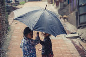 Two Children hiding themselves under an umbrella — Stock Photo