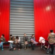 People sitting down on a red bench — Stock Photo #29469799