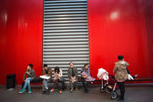 People sitting down on a red bench — Stock Photo