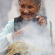 Eldery woman burning incense, Kathmandu — Stock Photo #29473507