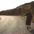 Old Woman walking on the road at the shore-line of Folegandros — Stock Photo #29475397