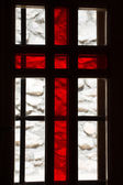 Stained window with red cross in a church — Stock Photo