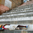 Legged sadhu sleeping on the stairs of a ghat, India — Stock Photo