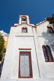 Facade of a typical white greek orthodox church with a clear blu — Photo