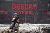 Niño en frente de roadsign, tíbet — Foto de Stock
