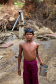 Young boy carrying water at the water pump in India — Stock Photo