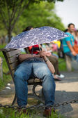 Sleeping man with an umbrella in a park in Hangzhou — Stock Photo