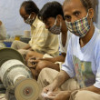 Masked artisans working for Tara, a Fair Trade Organization base — Stock Photo