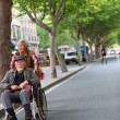 Woman pushing an old man in a wheelchair in the street of Shangh — Stock Photo