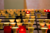 Burning candles in a church at Lourdes — Stock Photo