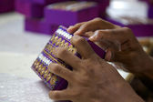 Close-up of hands working on a purple box in India — Stock Photo