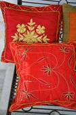 Bunch of decorative red satin shiny pillows — Stock Photo