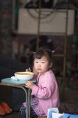 Young girl Eating on a blue table in Shanghai — Stock Photo
