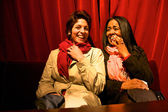 Two girls laughing at the theatre with a red curtain in the back — Foto Stock