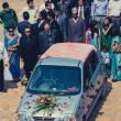 Group of people walking behind the lovers car at a public weddin — Stockfoto