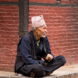 Old man resting and obsertving the street activity in Nepal — Стоковая фотография