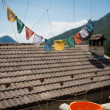 Prayer flags on a roof with a blue sky — Stock Photo