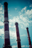 Dramatic sky and three industrial chimneys — Stock Photo