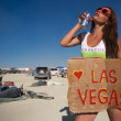 Sexy woman holding a sign with Las Vegas while drinking — Stock Photo