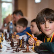 Serious little boy playing chess with other students — Stock Photo