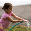 Cute curly girl watering flowers in the garden — Stock Photo