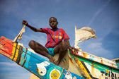 Kid sitting on a colored fisher boat in Senegal — Zdjęcie stockowe