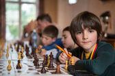 Grave ragazzino giocare a scacchi con altri studenti — Foto Stock