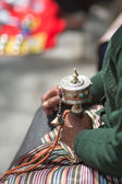 Old woman praying with prayer roll in Lhasa — Stock Photo