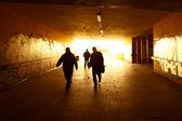 Silhouetten, die zu fuß in einen städtischen grunge-tunnel — Stockfoto