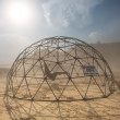 Dome structure in a dusty sand storm with information sign — Photo