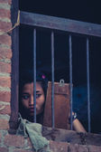 Young Nepalese girl looking to herself in the mirror at home, Bh — Stock Photo