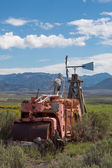 Skeleton sitting on a vintage tractor in Utah with mountains — Stock Photo