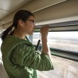 Chinese young woman looking by an open window in train — Stock Photo
