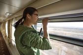 Chinese young woman looking by an open window in train — 图库照片